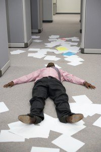Businessman on floor surrounded by papers