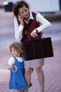 Mother talking on a mobile phone with her daughter standing beside her